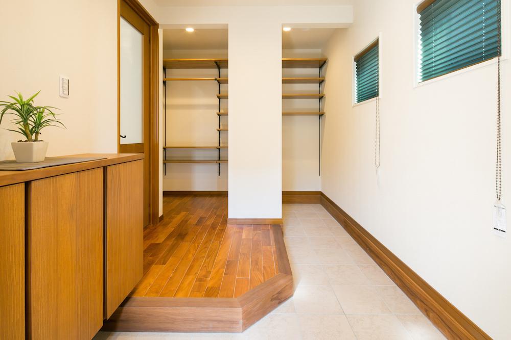 玄関ホールにはあえて見せる収納棚。